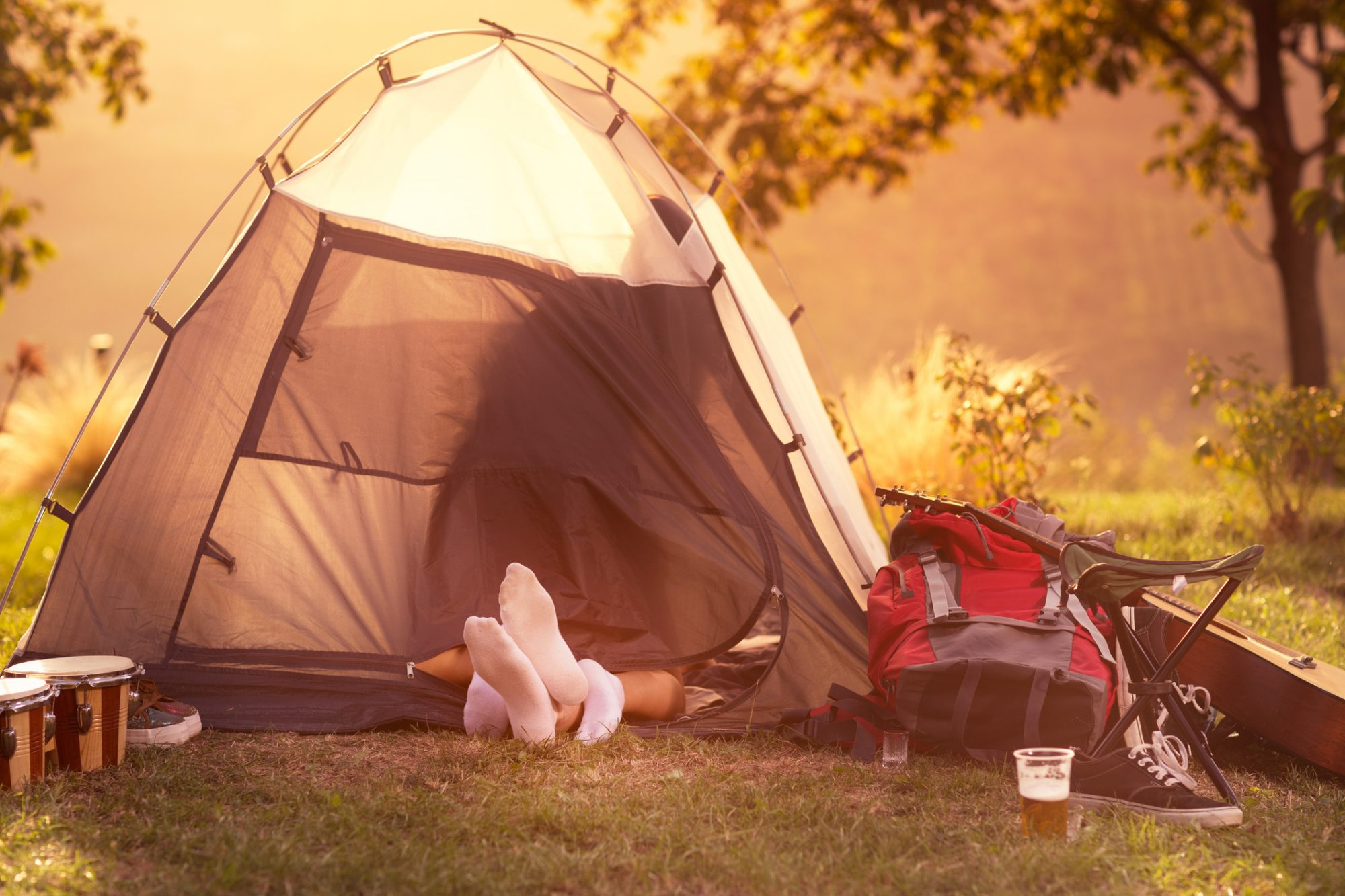 Young couple having safe sex in tent