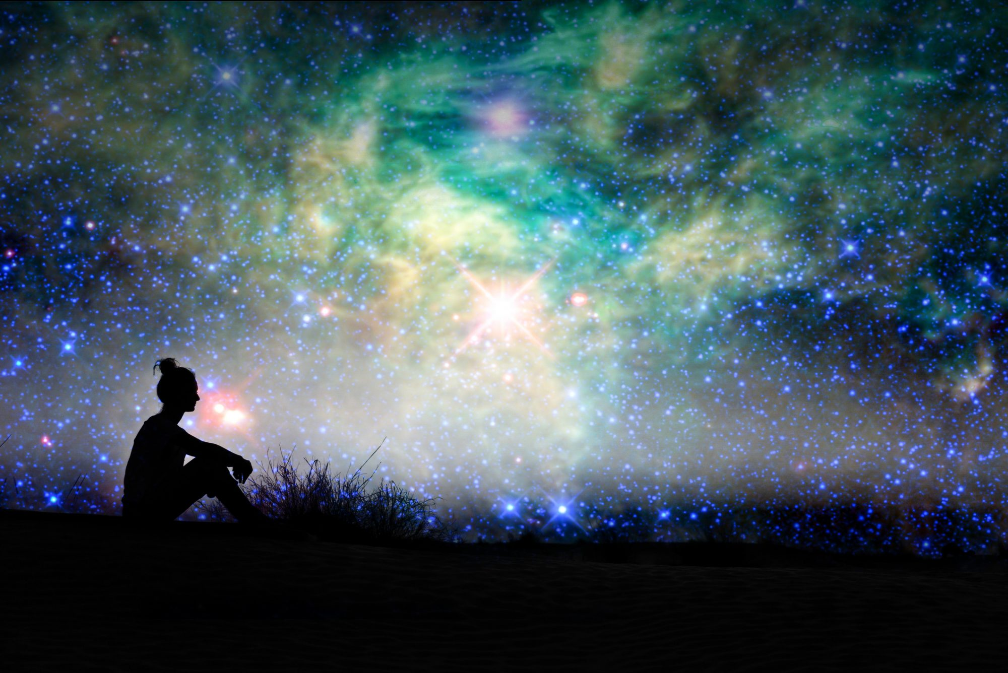 silhouette of a woman sitting under the stars