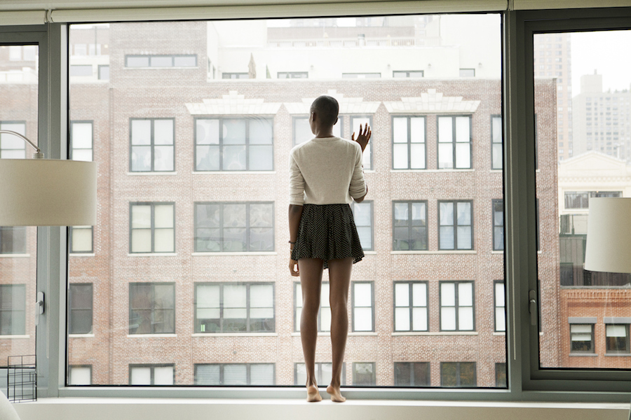 Woman looking out her window from apartment
