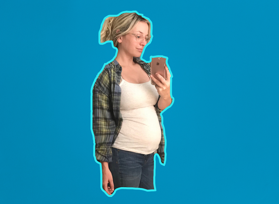 Author taking a selfie of her pregnant belly on a blue background