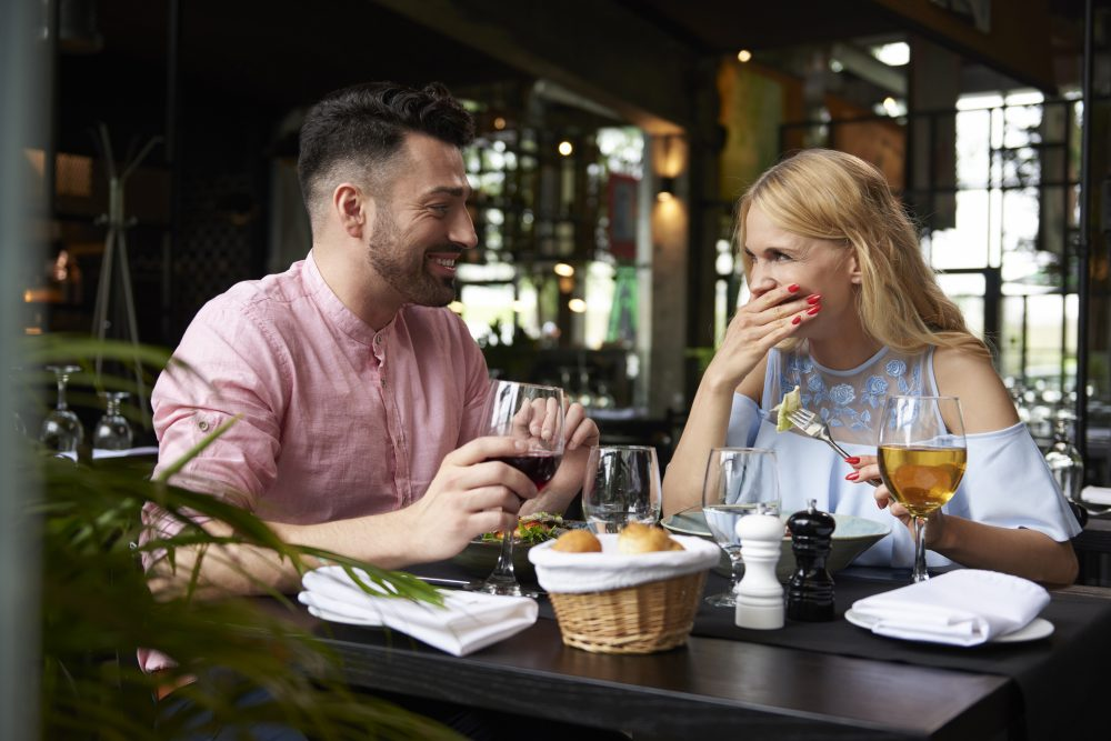 guy and girl flirt at restaurant on date