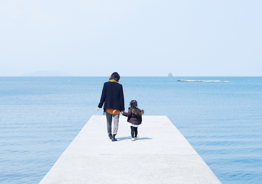 Mother and child holding hands on pier
