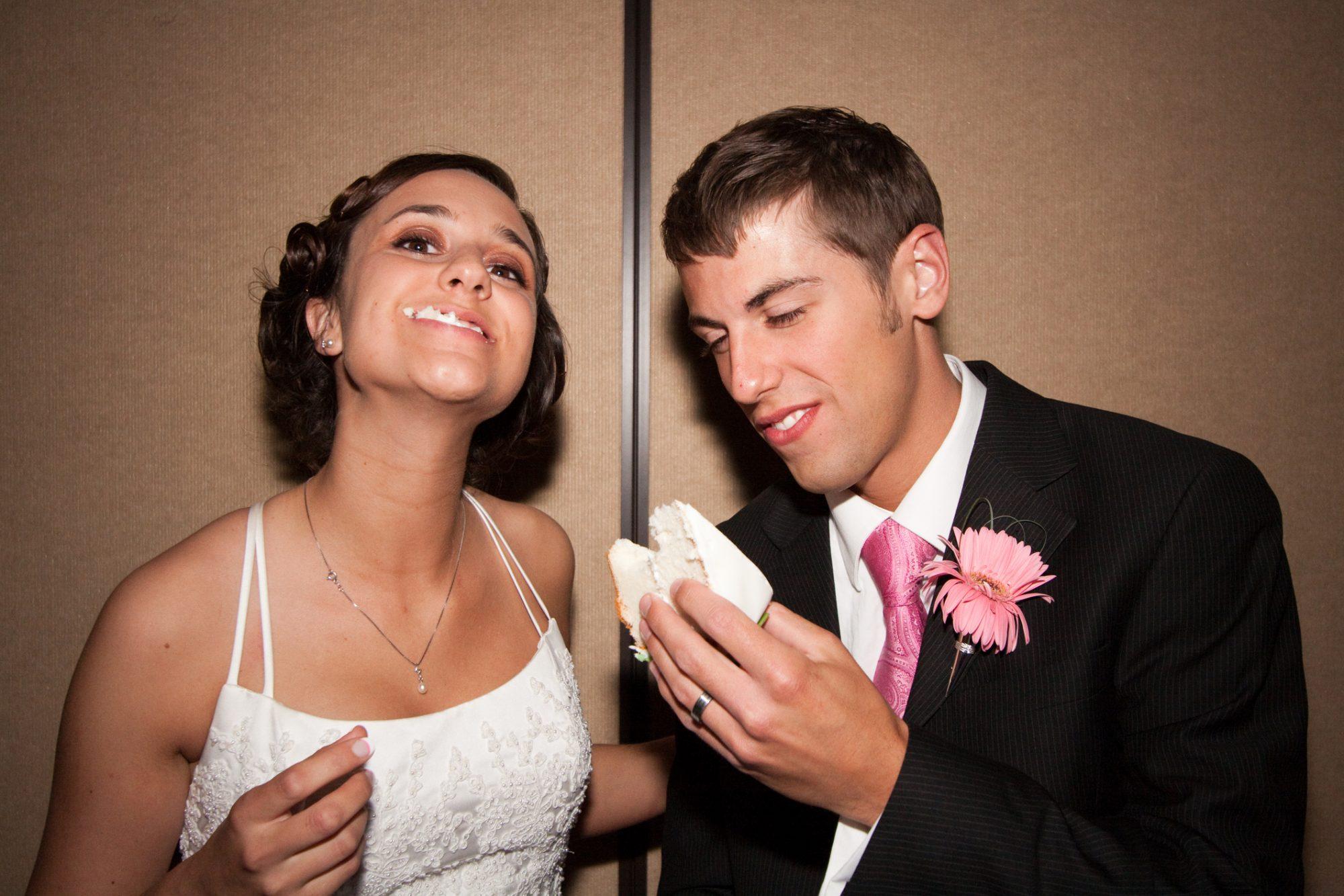 Newlyweds take bites of cake at a wedding reception