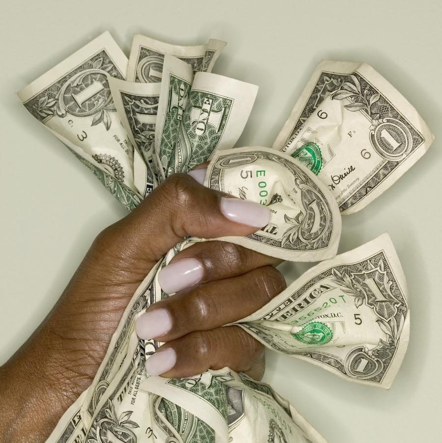 Woman's hand gripping dollar bills