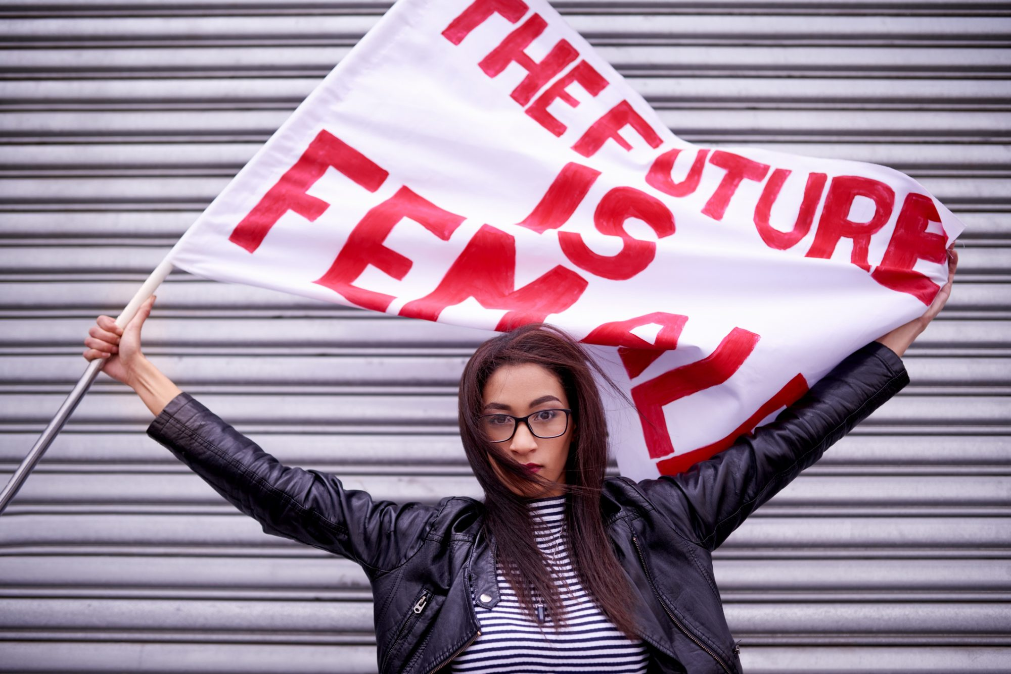 """Portrait of a woman holding a flag that reads """"The future is female"""" protesting in the city"""