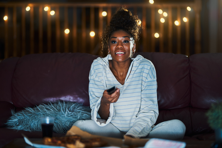 Woman binge-watching TV on her couch at night