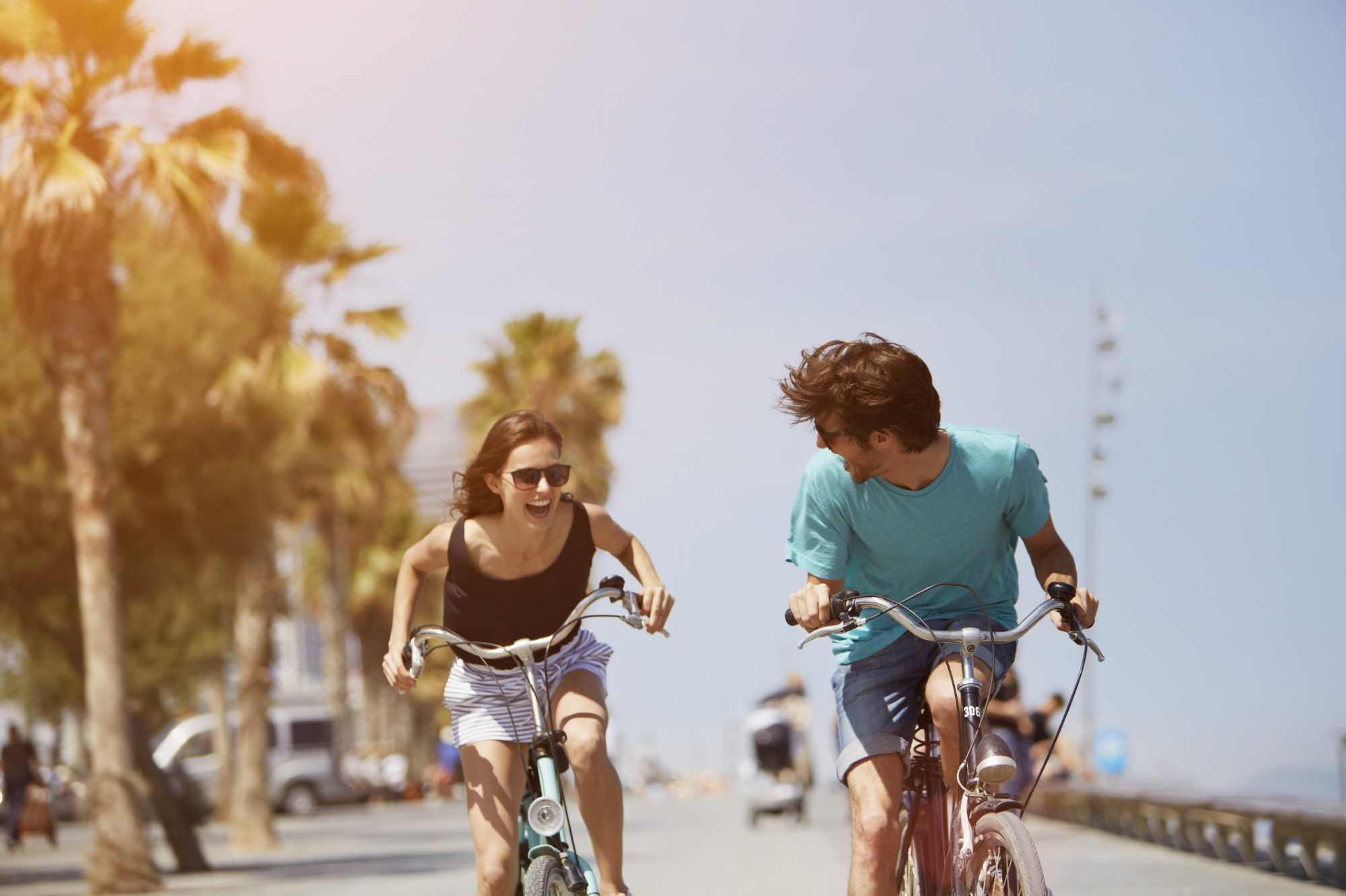 Happy young woman chasing man while riding bicycle during summer vacation
