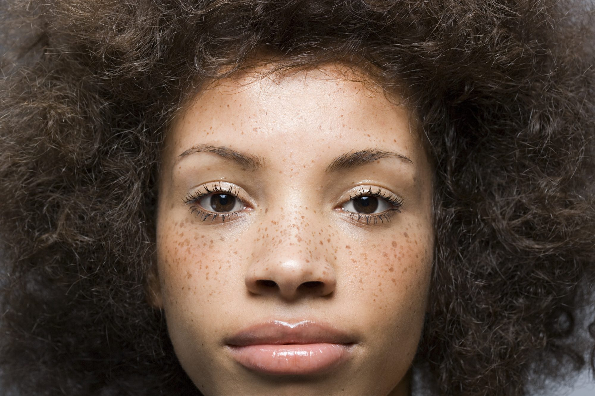 A closeup of a young woman with freckles on her face