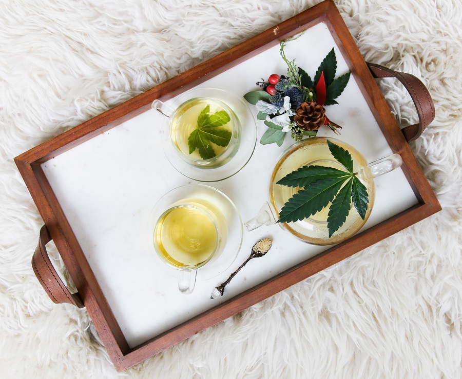 tray with tea and marijuana leaves
