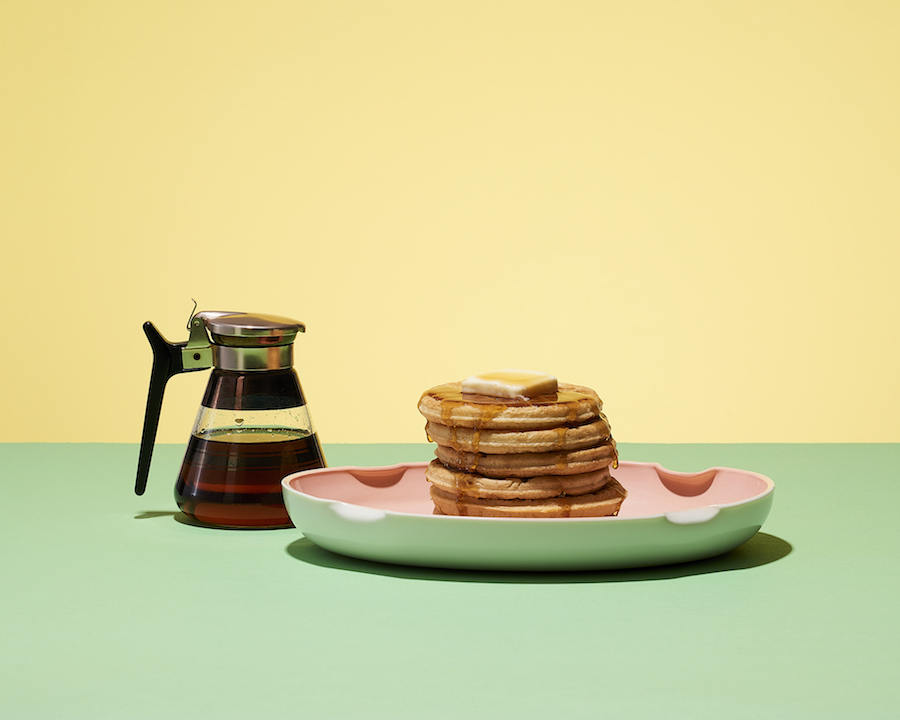 Pancakes and syrup on a yellow and green background