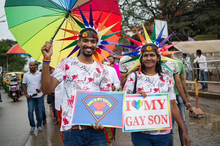 Mother and son at Pride parade. Mom is holding sign that says, 'I love my gay son'