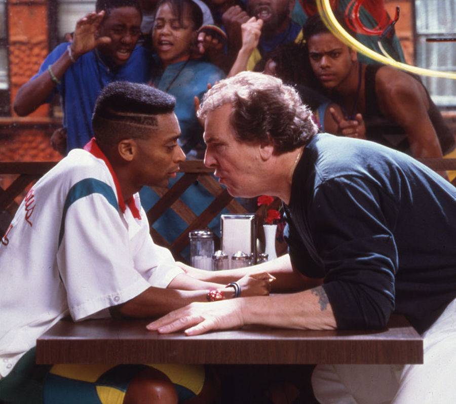"""Promotional image from Spike Lee's """"Dp The Right Thing"""" featuring Lee and actor Danny Aiello in an argument at a pizzeria as the neighborhood looks on"""