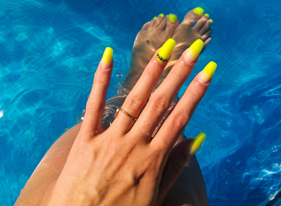 neon ombre nails in gel manicure woman in pool