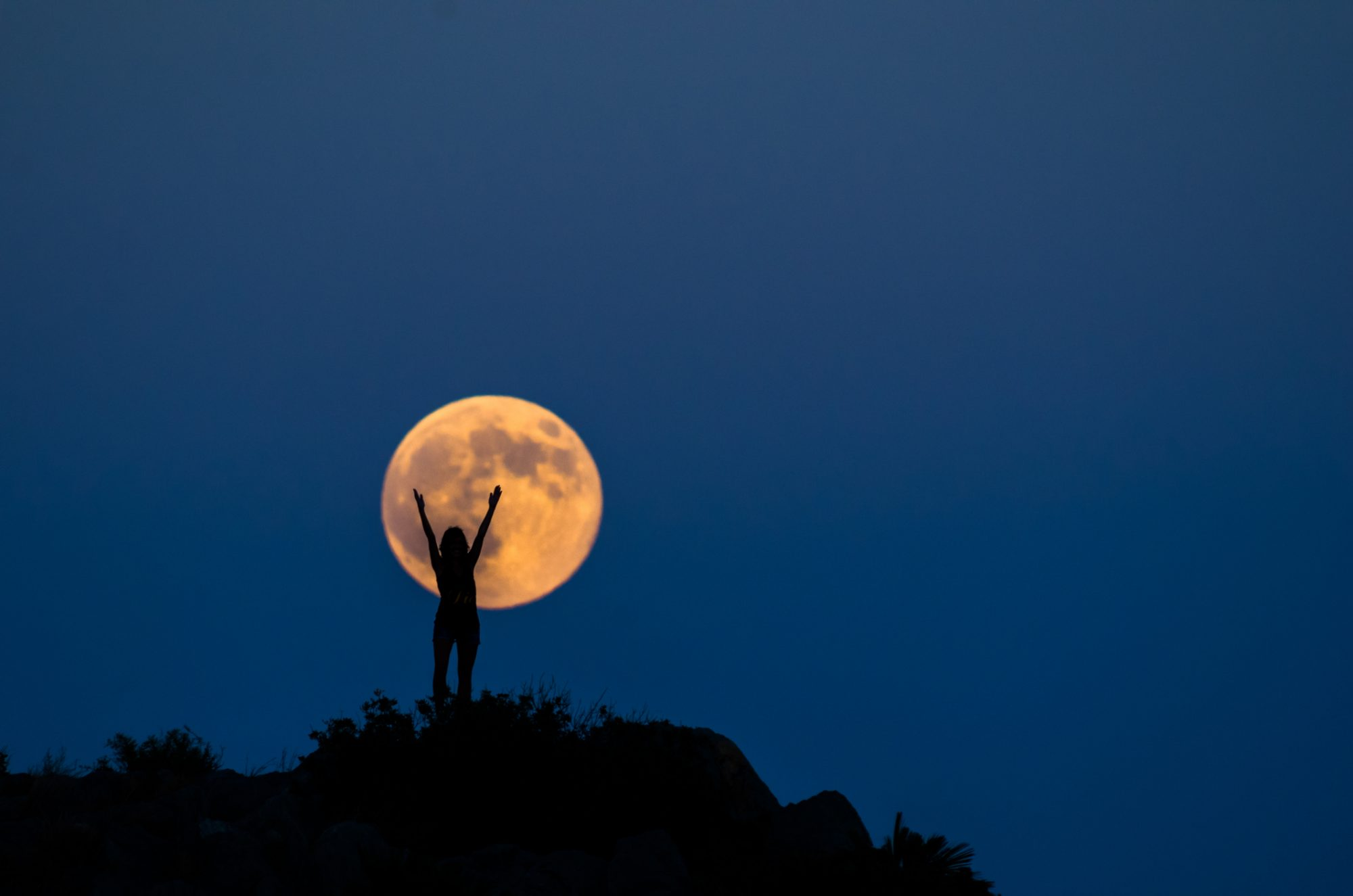 Silhouette of a woman raising her arms up in front of a full moon