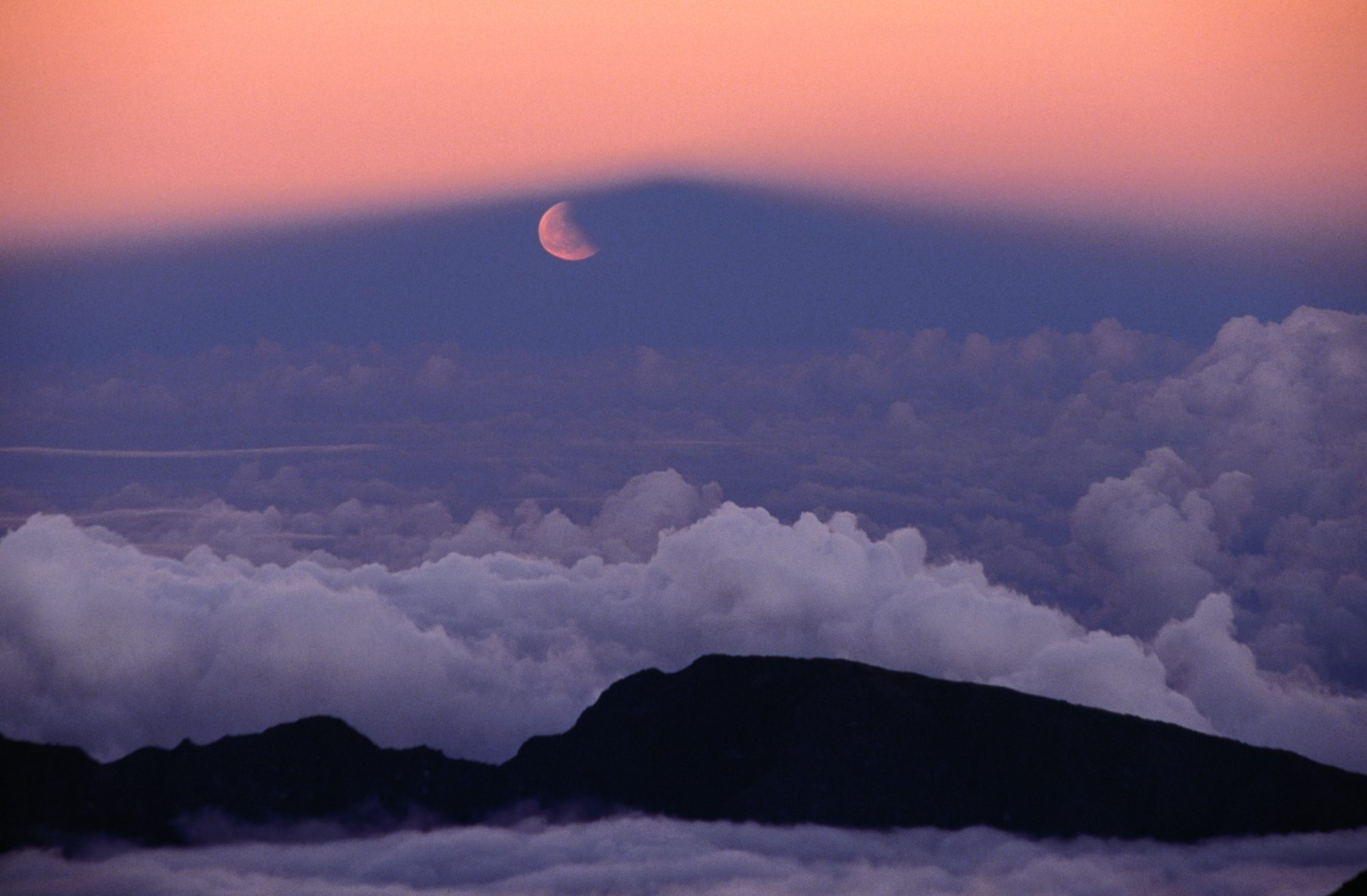 Lunar eclipse at sunset with a moonrise from the summit of Mt Haleakala