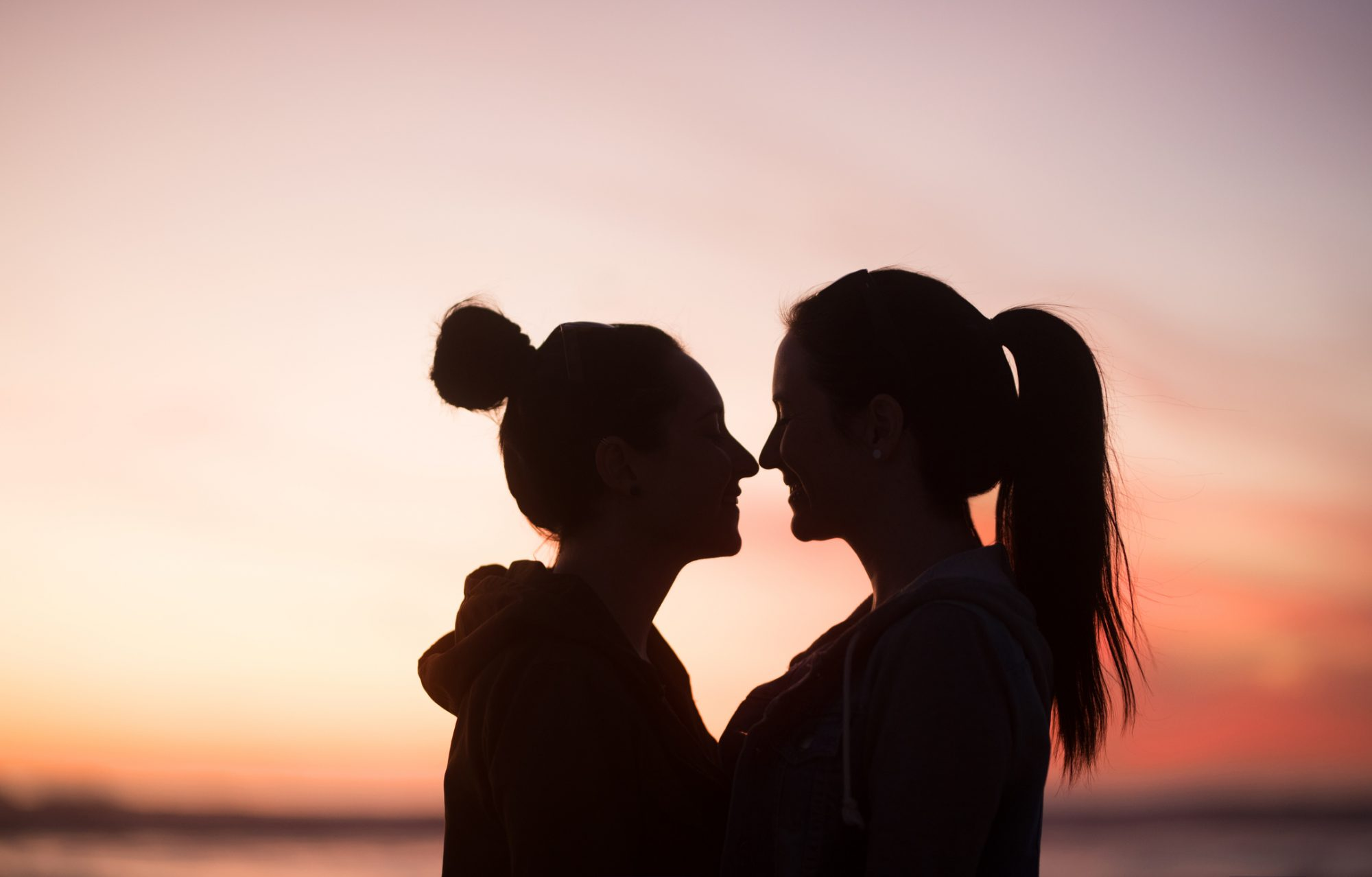 Outline of two young women standing very close to one another looking at each other at sunset