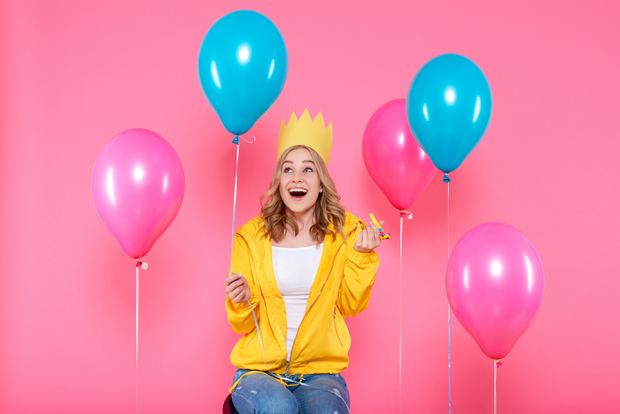 Woman celebrating with balloons and a party hat