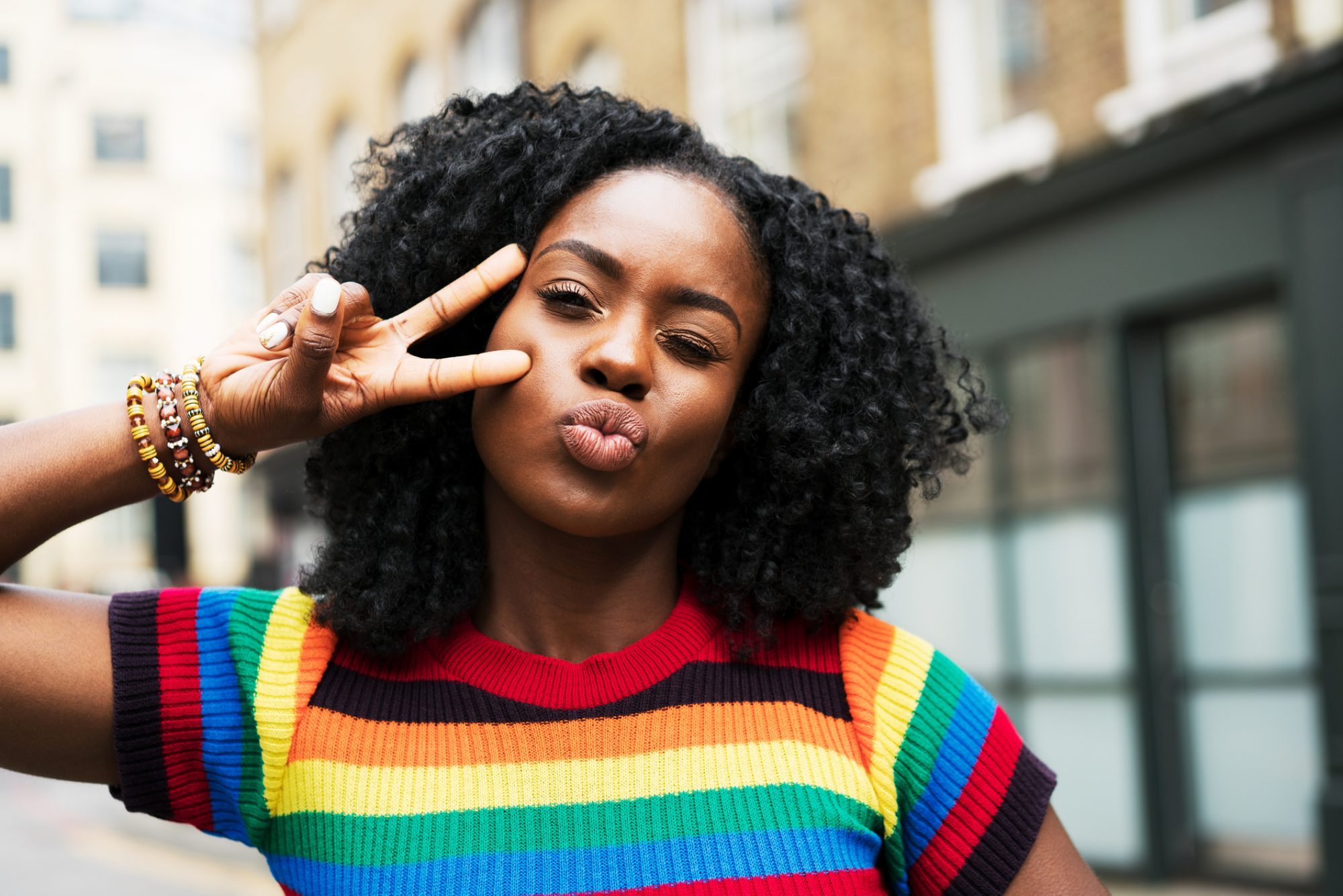 Woman making a kiss face and posing with a peace sign