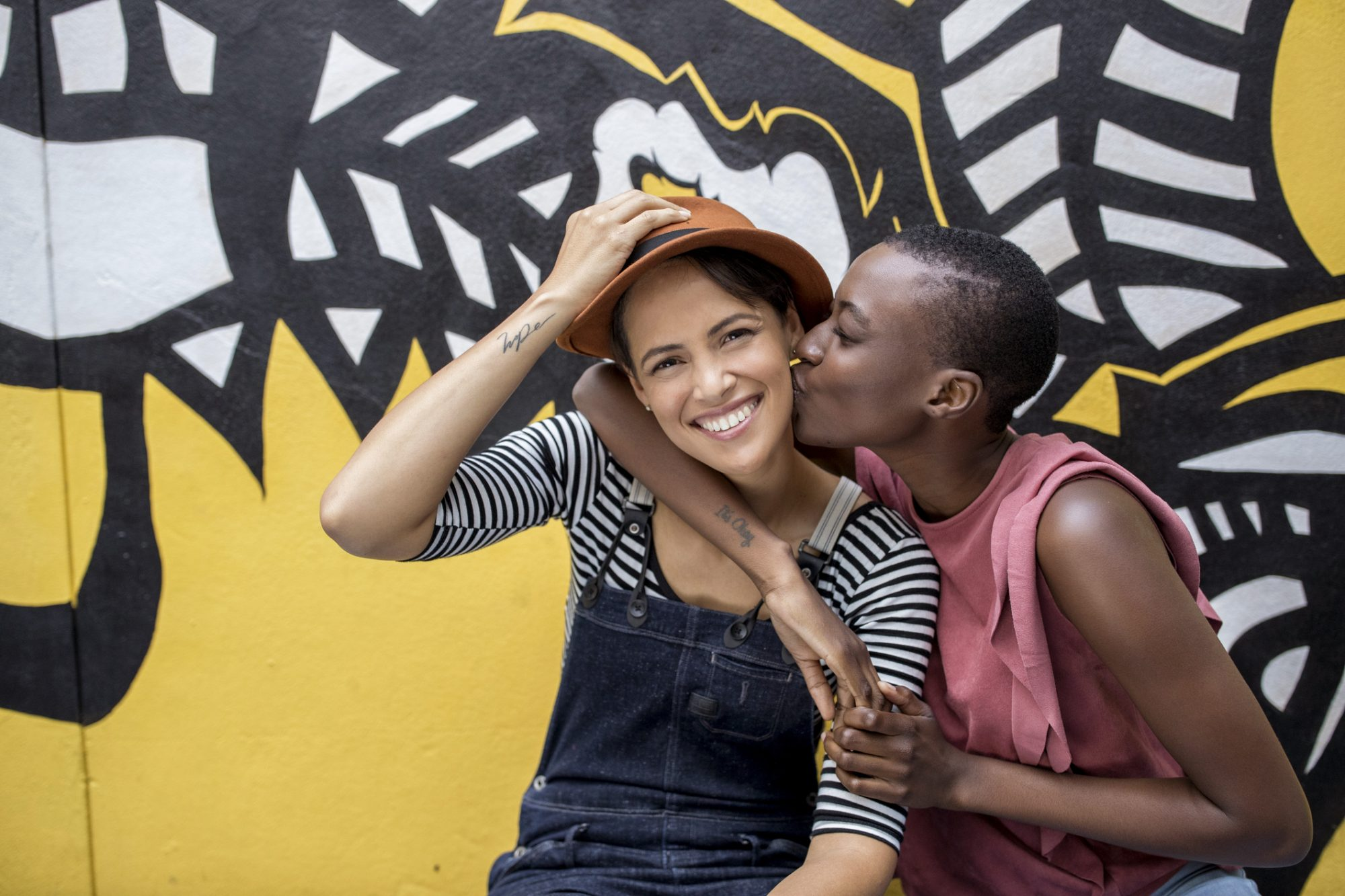 Young woman kissing girlfriend in front of graffiti wall