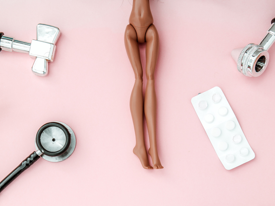 Doll legs surrounded by sexual health objects
