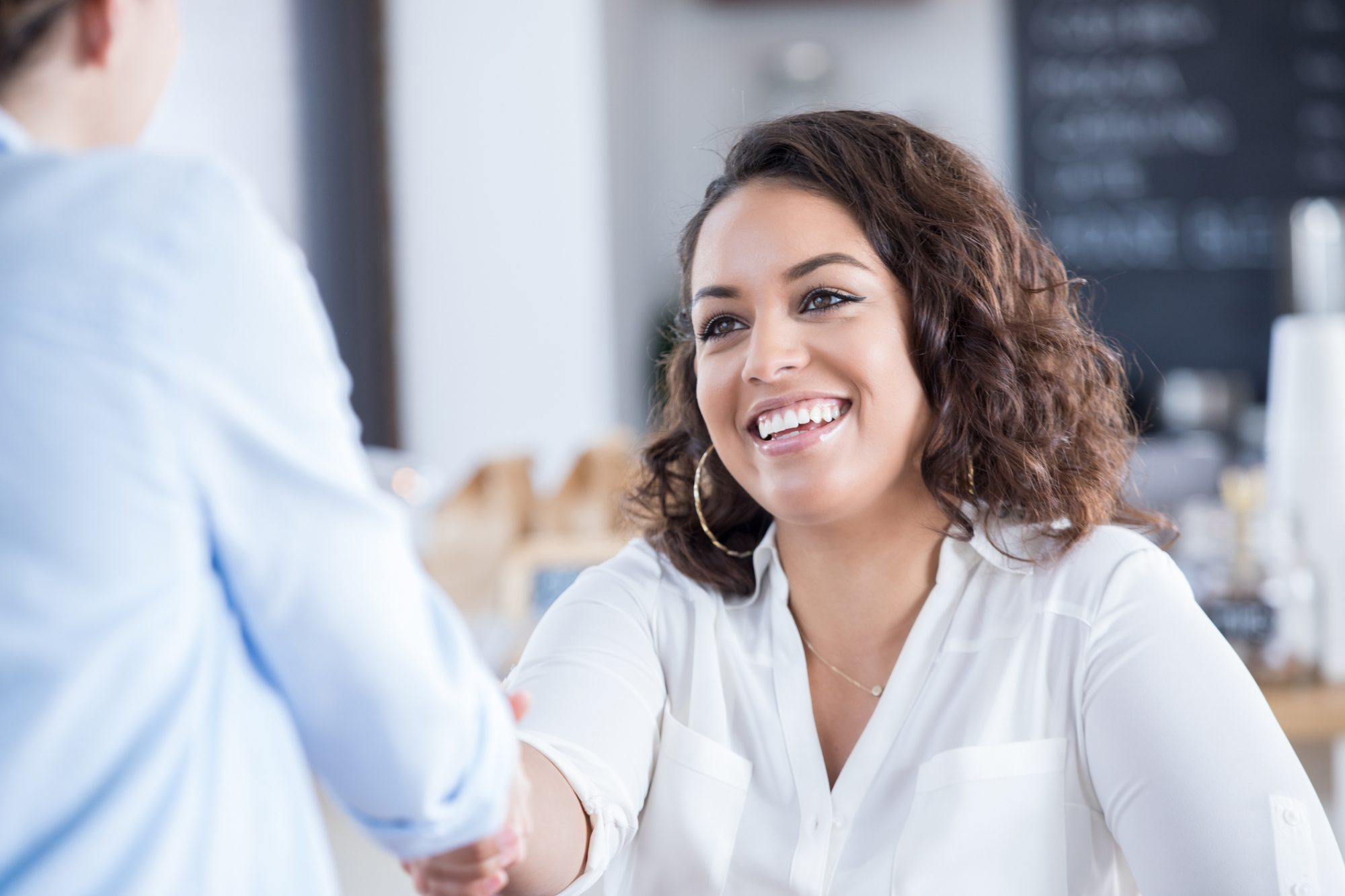 Young woman shaking hands with a colleague in coffee shop