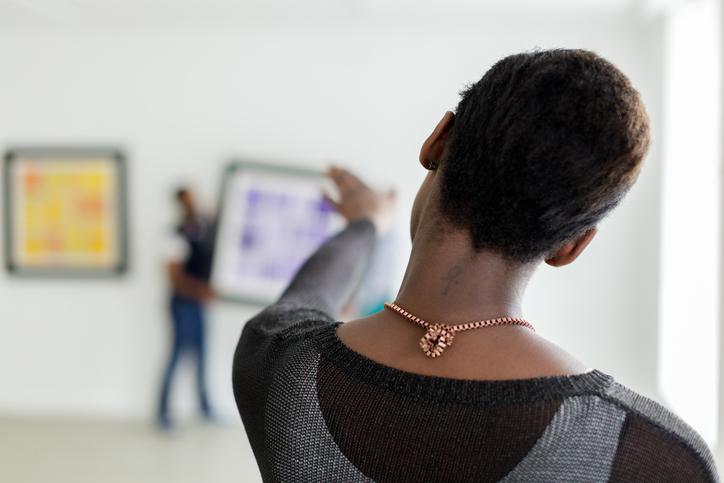 Black woman supervising art being mounted in gallery