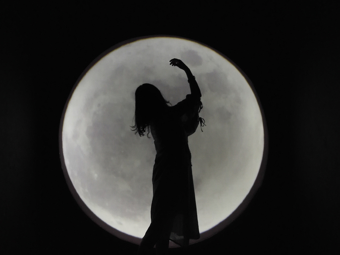 Woman's silhouette in front of full moon