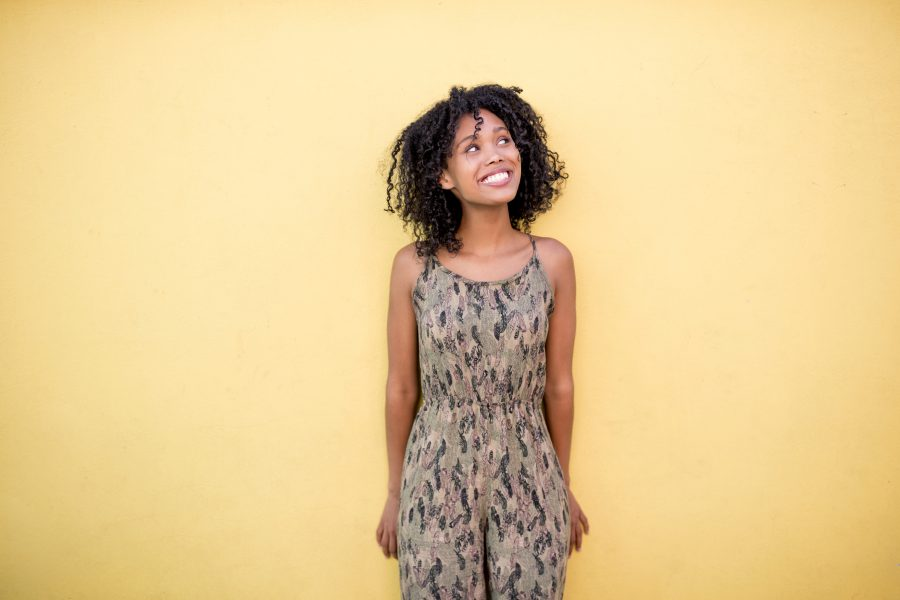 Smiling young woman with curly hair standing in front of yellow wall