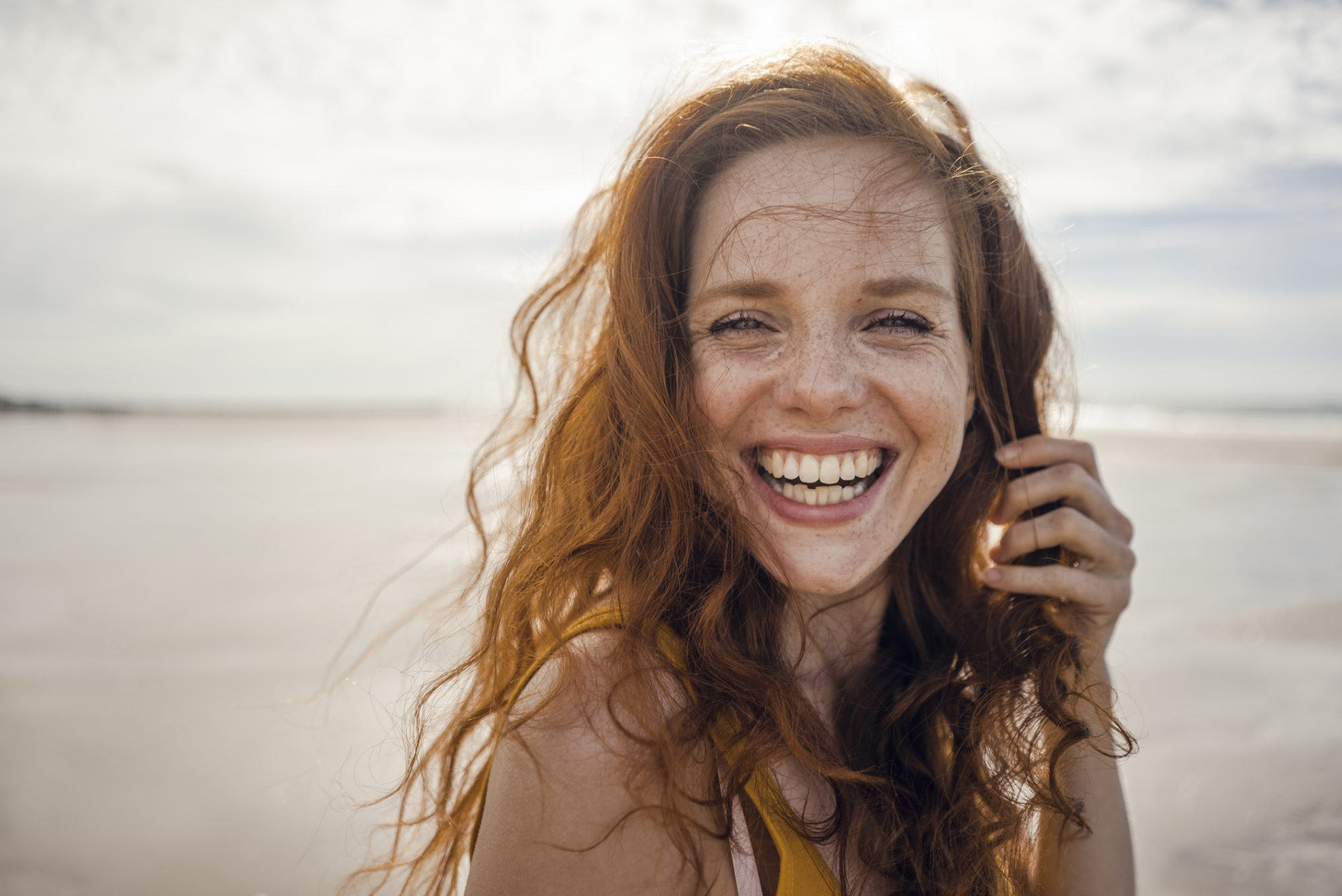 Portrait of a redheaded woman, laughing happily on the beach