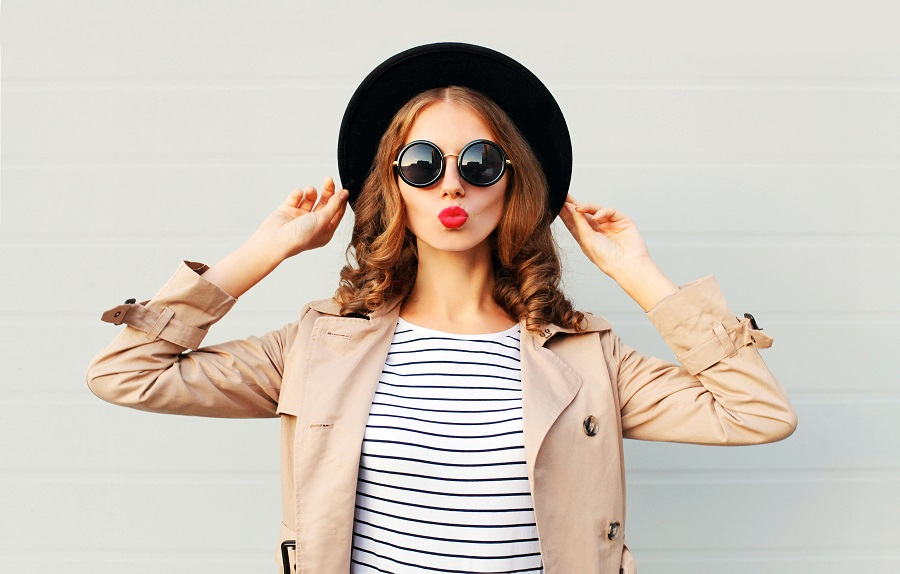 woman wearing summer to fall transitional pieces like a trench and hat