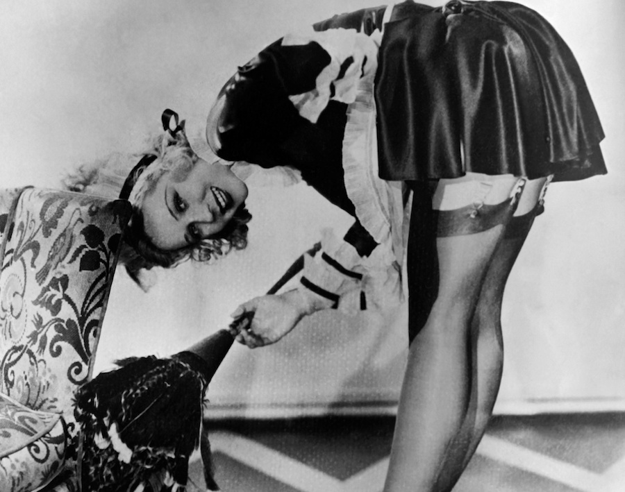 Actress Adrienne Dore bent over in a black and white pin up girl photo from the 40s or 50s