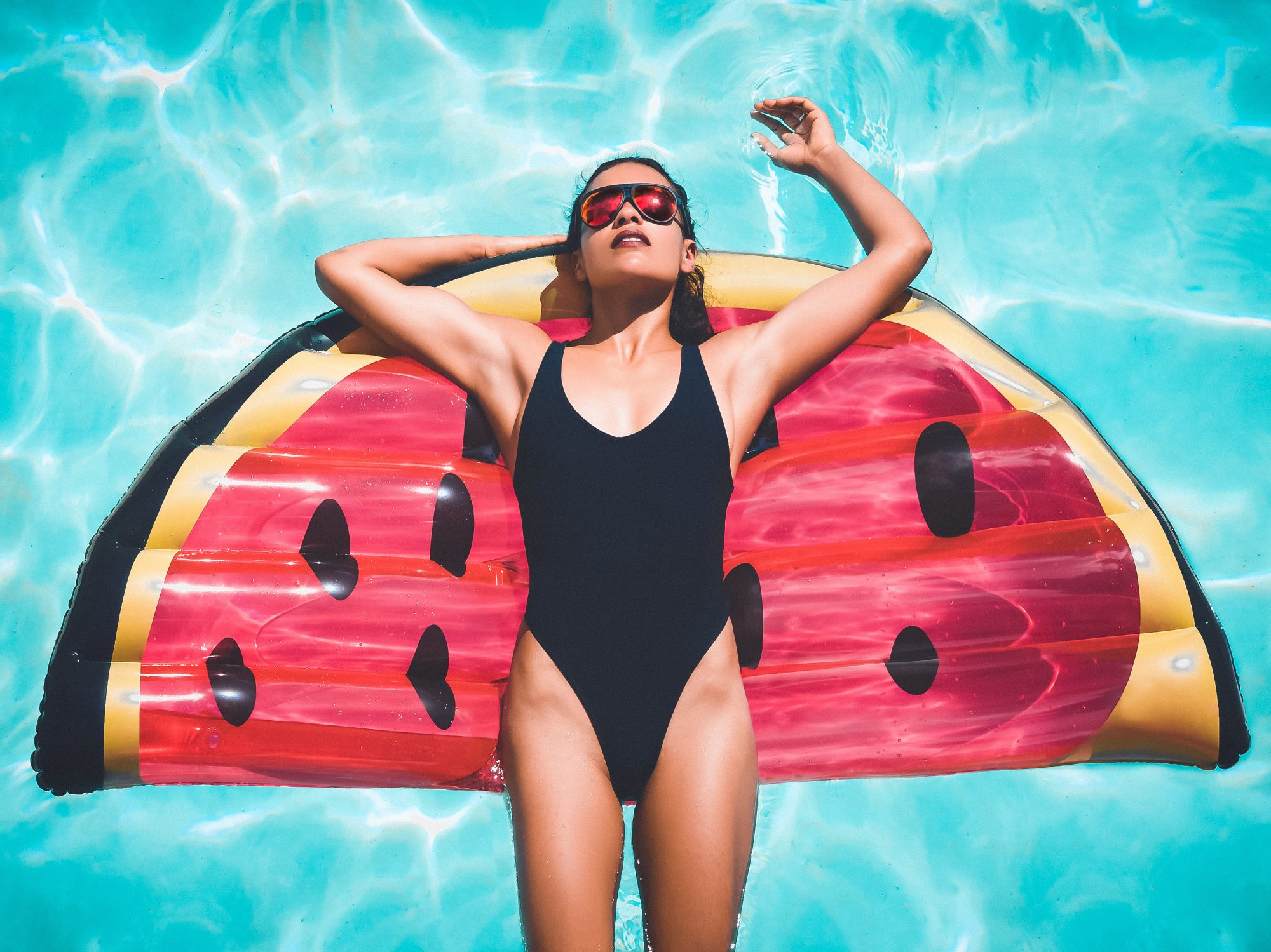Directly Above Shot Of Woman In Swimwear Relaxing On a Watermelon Pool Float