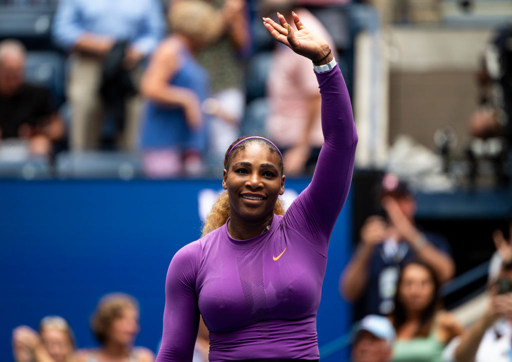 Serena Williams smiles and waves on the tennis court