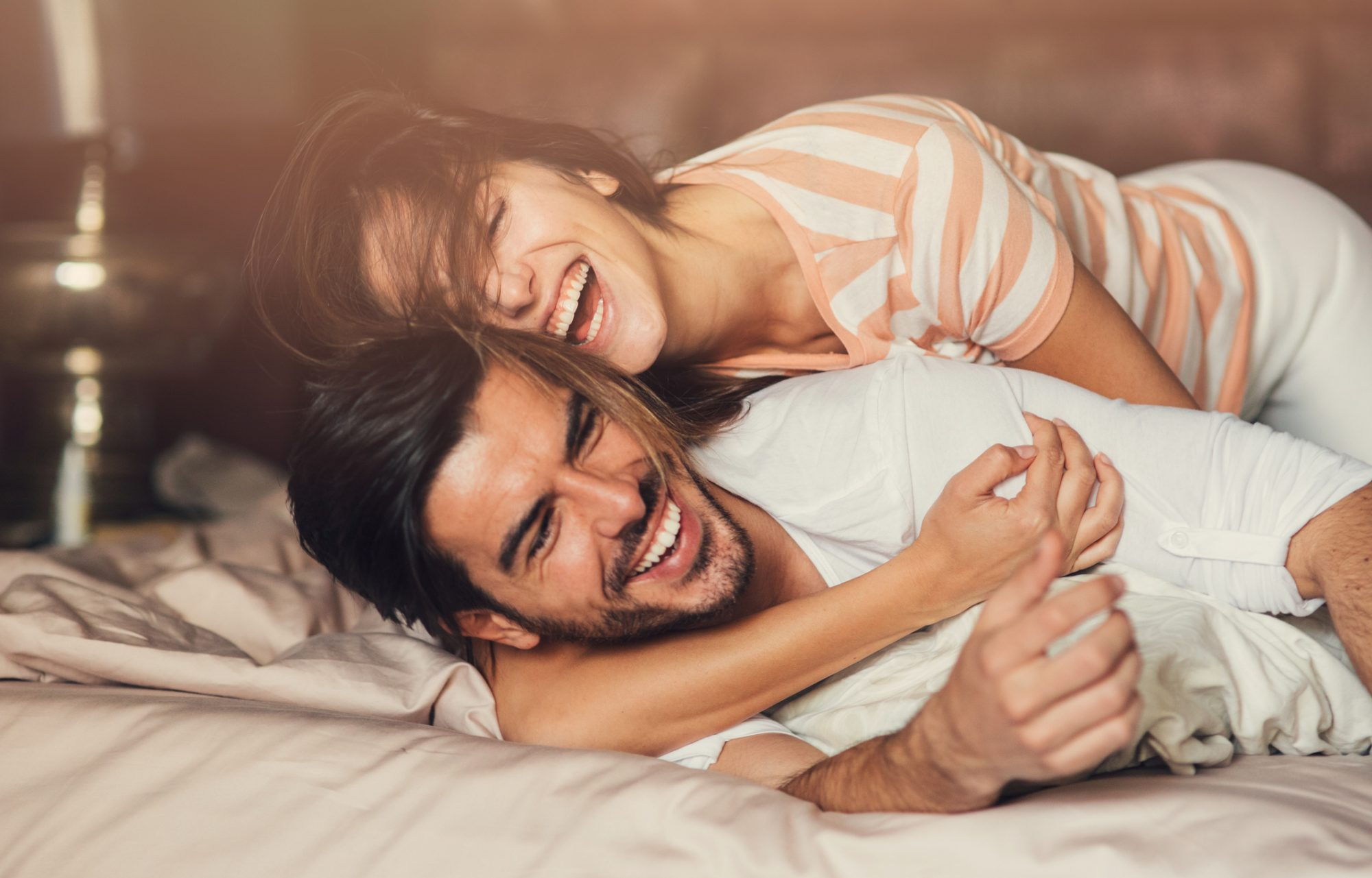 Happy young playful couple in bed