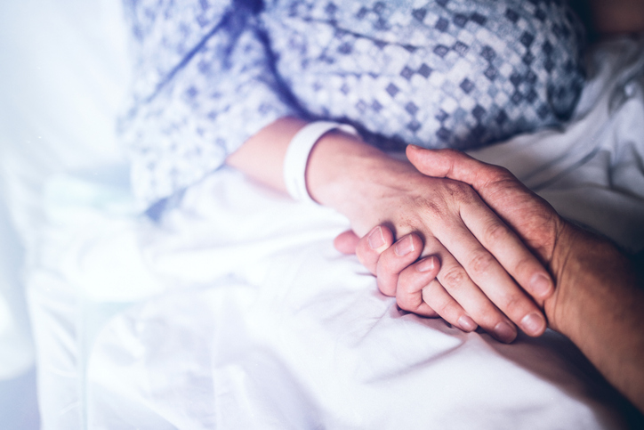 Husband holding wife's hand in hospital