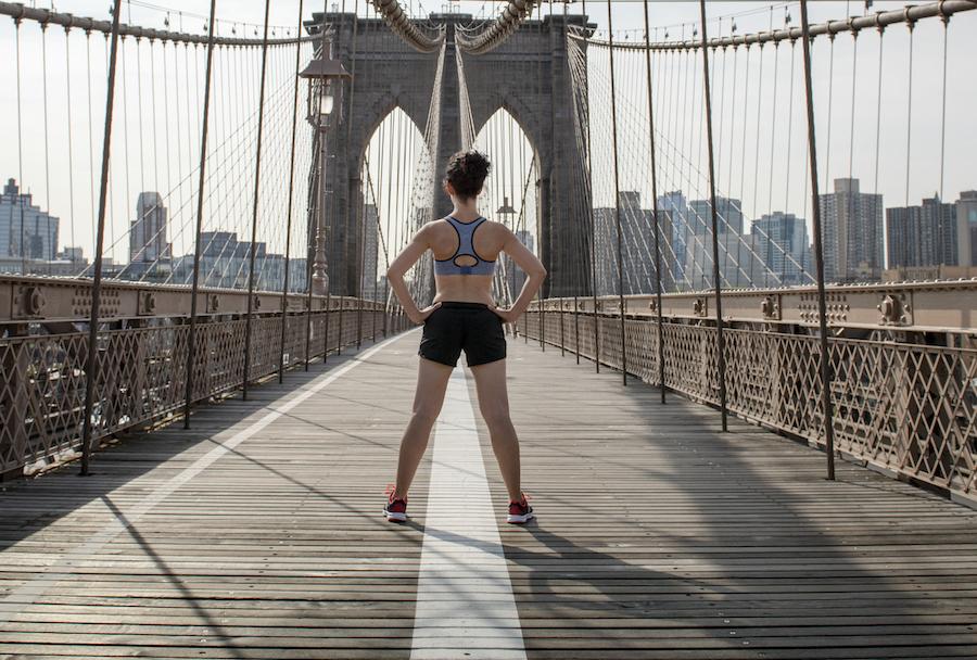 Marathon runner standing on a bridge