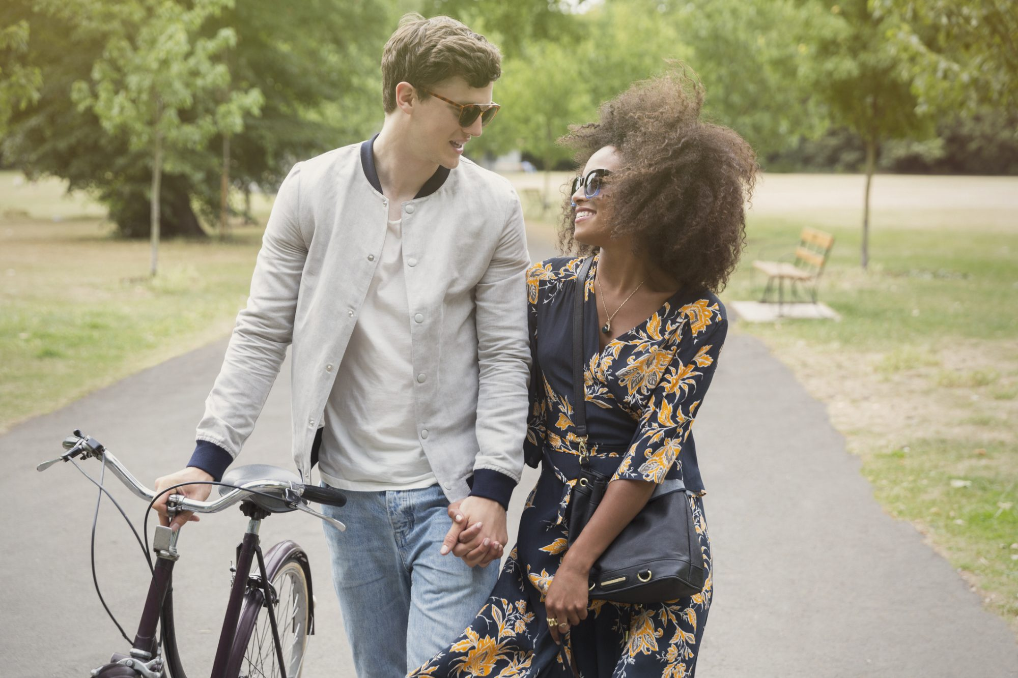 Couple walking with bicycle in park