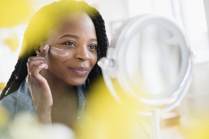 Black woman applying sunscreen in mirror