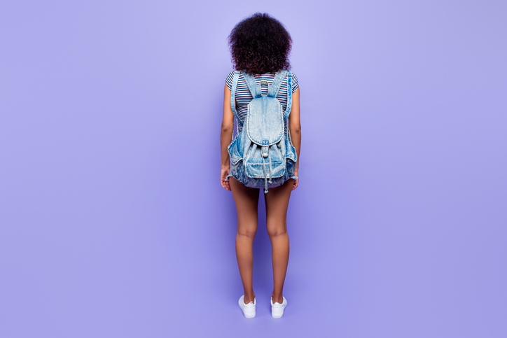 Rear view of girl wearing backpack and standing in front of purple wall