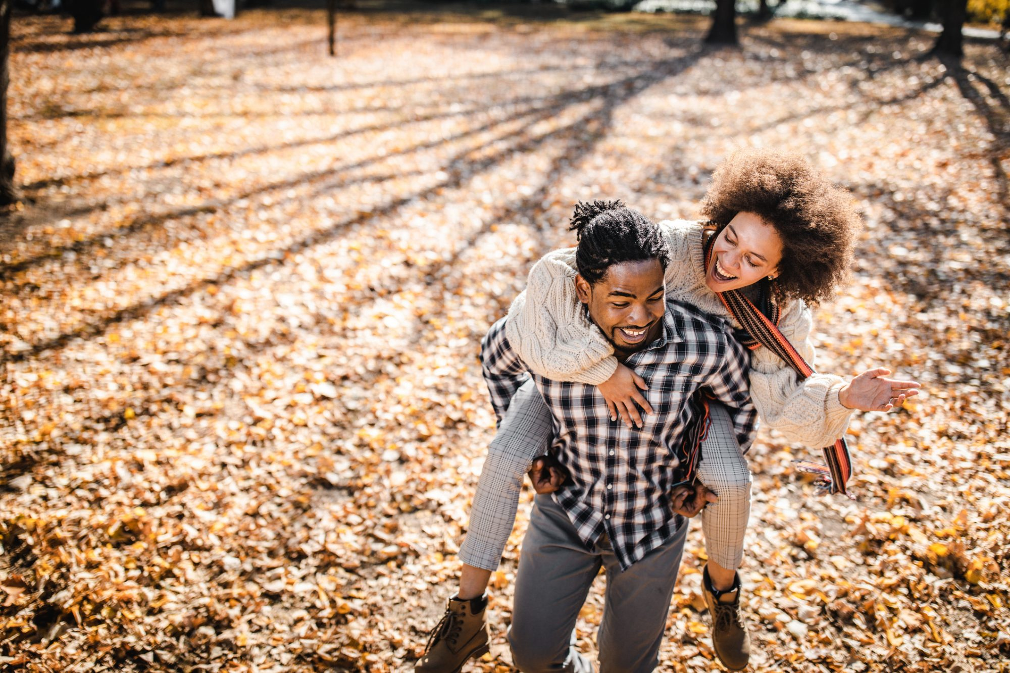 Cheerful couple piggybacking in autumn at the park