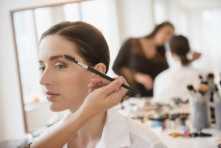eyebrow feathering woman with makeup artist