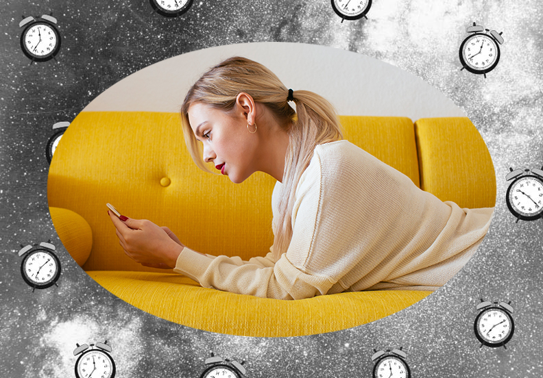 Blonde woman laying on the couch and looking at her phone