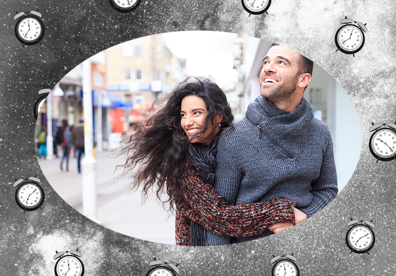 Woman smiling and hugging man on the sidewalk during fall