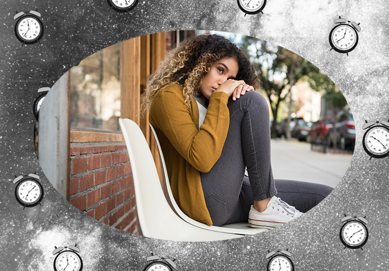 Pensive woman sitting on a white chair on a city sidewalk