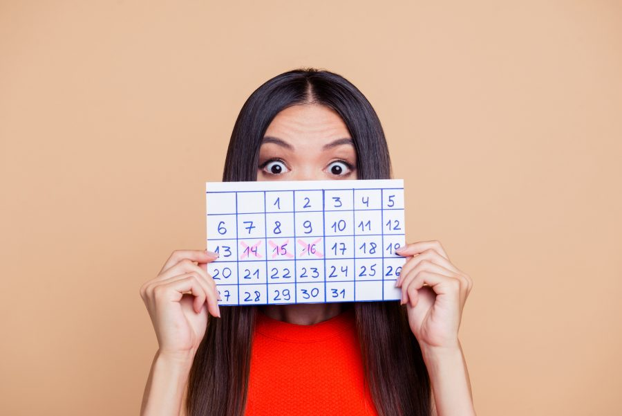 woman holding up calendar period came early