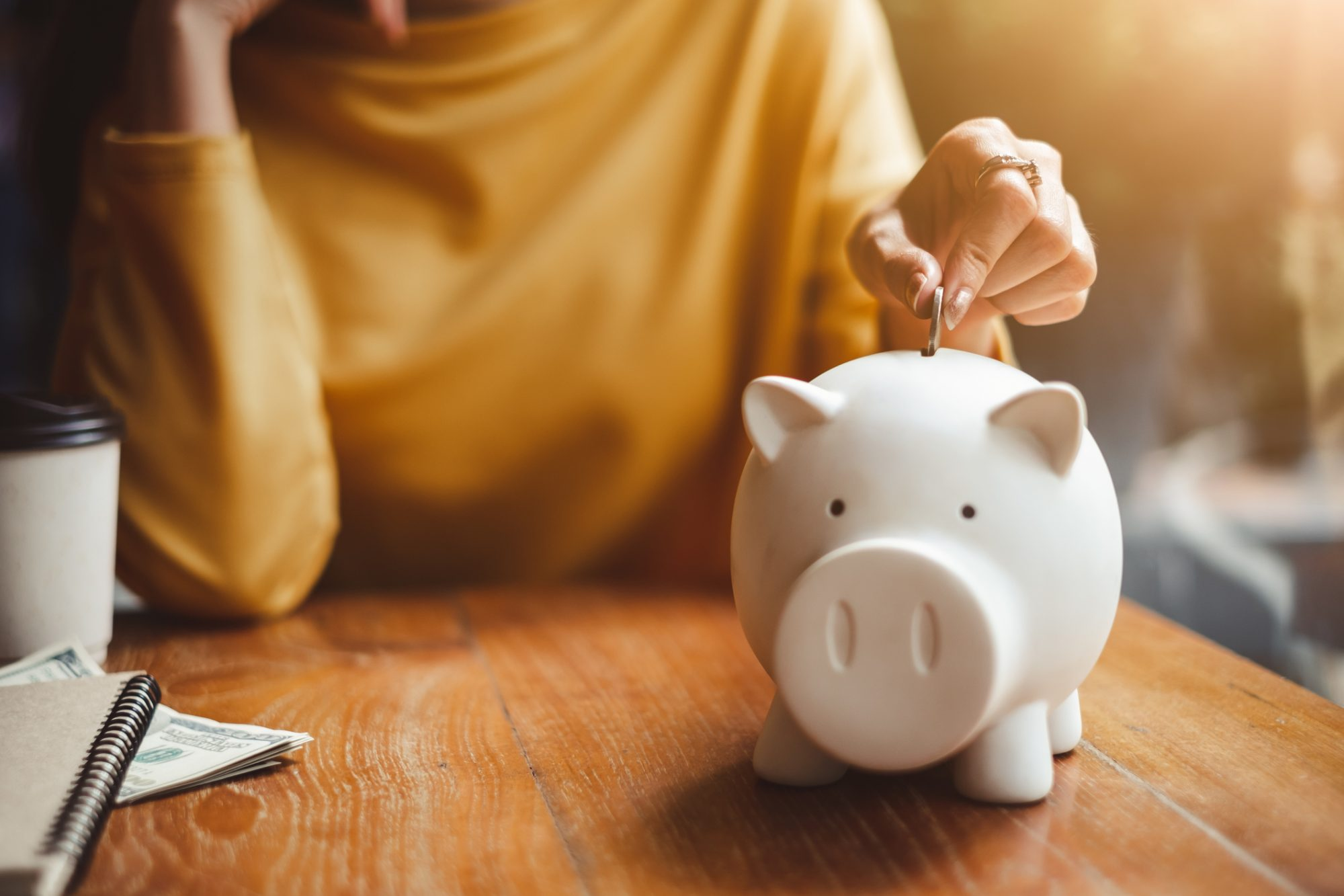 Woman Putting Coin In Piggy Bank On Table At Home