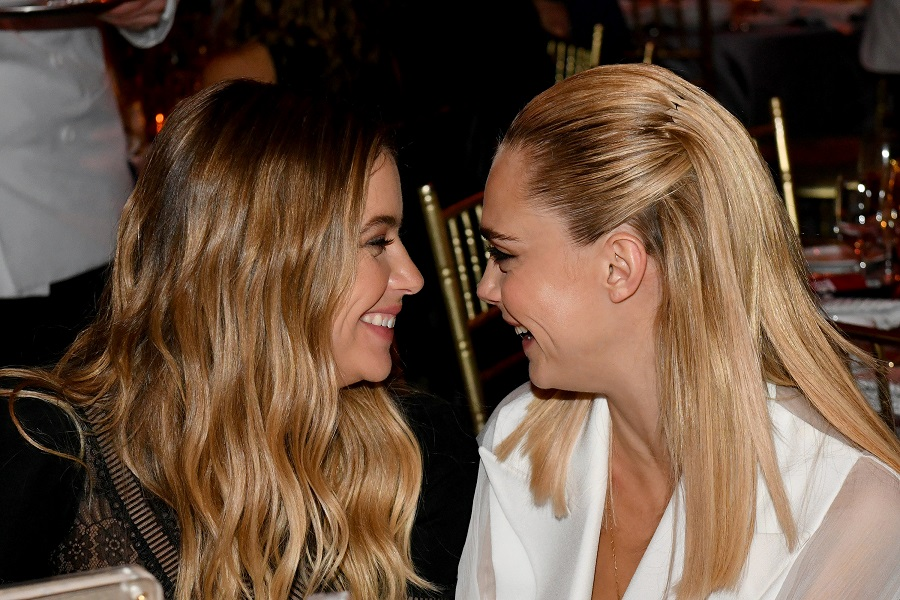 Ashley Benson and Cara Delevingne smiling at each other