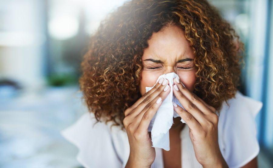 coronavirus versus allergies woman sneezing
