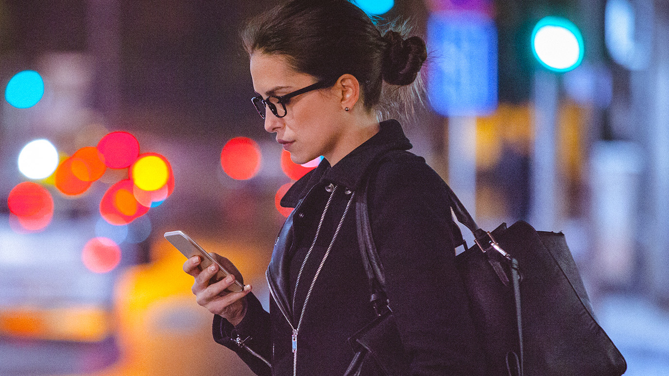 Woman holding a phone while walking on the street in the dark