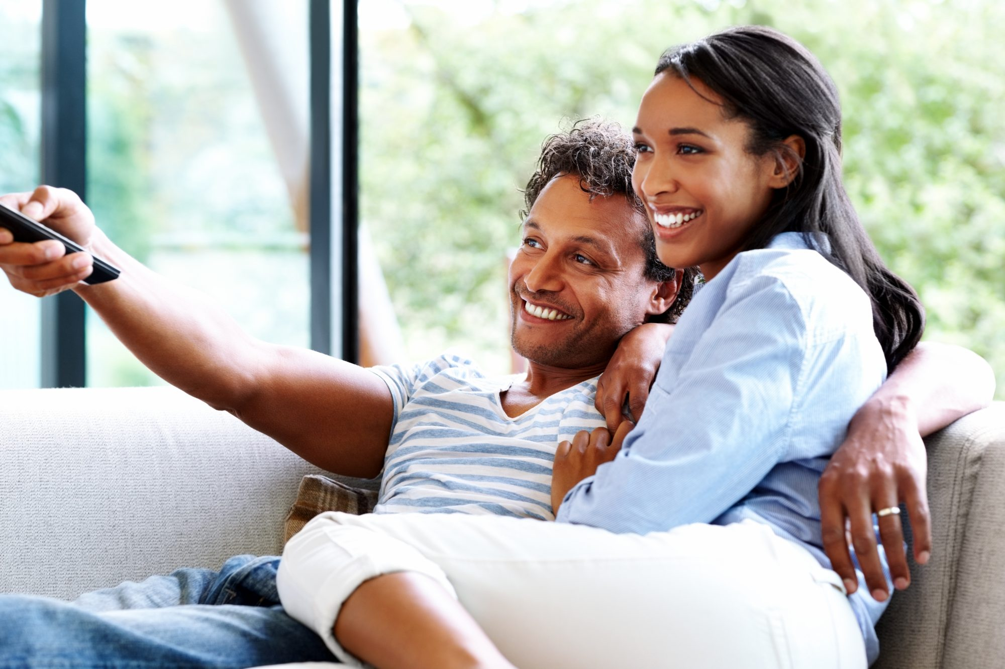Couple sitting on the couch watching TV